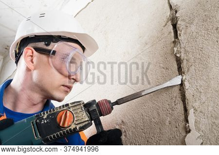 Builder In Safety Glasses And Helmet Drills A Wall With A Perforator, Side View