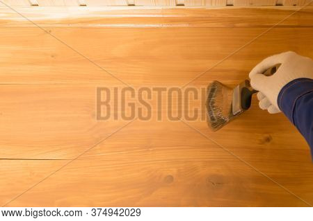 Empty Covered Wooden Surface With Dark Varnish In The Corner Hand With Brush