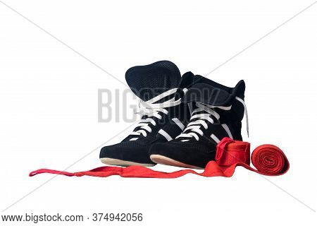 Black Wrestling Shoes And Unwound Red Protective Bandages For Martial Arts Isolated On A White Backg
