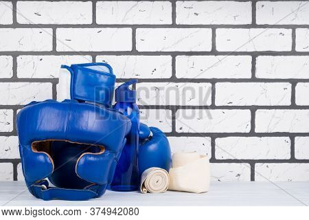 Blue Set Of Helmet And Boxing Gloves For Sports On The Background Of A Brick Wall, On The Right Ther