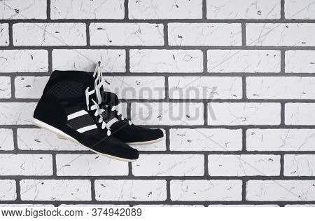 On The Background Of A Brick Wall Black Wrestling Shoes, On The Right There Is A Place For Inscripti