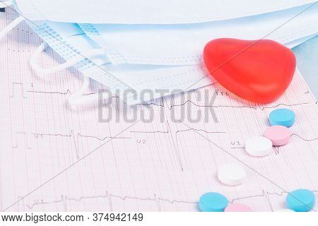Concept Of Protective Medical Masks, Vitamins And Red Heart On Ecg Background