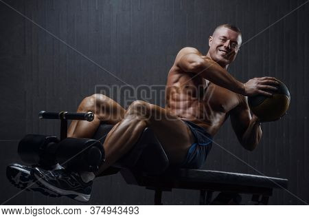 Fitness Man Pumping Up Abs Muscles In Gym