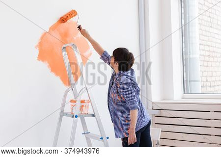 Happy Smiling Middle-aged Woman Painting Interior Wall Of New House. Redecoration, Renovation, Apart