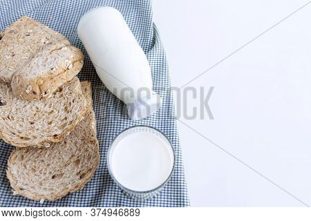 A Bottle Of Milk And Glass Of Milk With Sliced Bread On Cloth Indoors Background For Food And Health