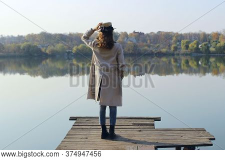 Young Girl Wearing A Beige Trench Coat, Jeans And Black Boots, Standing On A Wooden Bridge And Looki