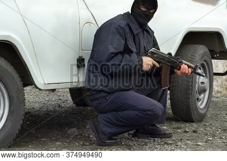 Masked Terrorist Holding A Rifle Gun In His Hands Near The Car. Terrorist With Weapon After Attackin