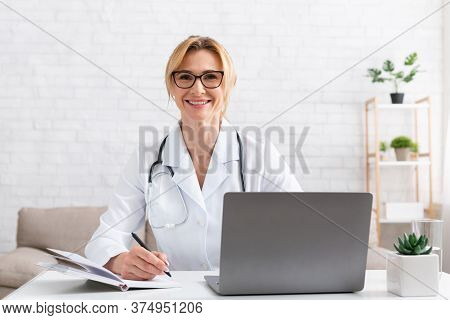 Therapist Online. Smiling Woman Doctor At Workplace With Laptop And Notepad In Interior, Copy Space