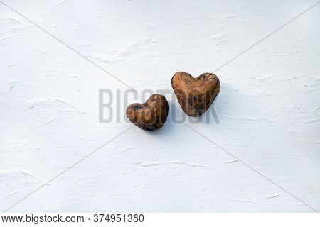Two Raw Potatoes. Potatoes Like A Heart. Two Raw Potatoes On The White Wooden Background. Potatoes L
