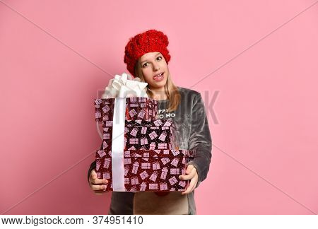Teenage Female In Gray Plush Pajamas, Red Hat With Pompom. She Holding Colorful Gift Boxes Tied With