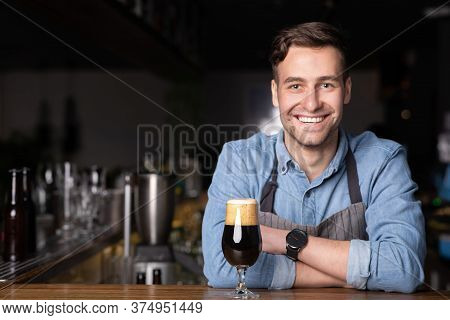 Dark Craft Beer With Foam In Glass. Modern Smiling Barman In Apron With Crossed Arms In Interior Of