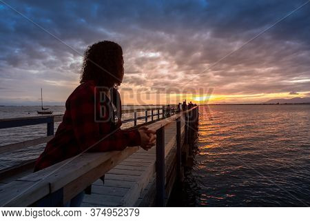 Girl Watching Beautiful Sunset On A Wooden Quay At The Pacific Ocean. Taken In White Rock, Greater V