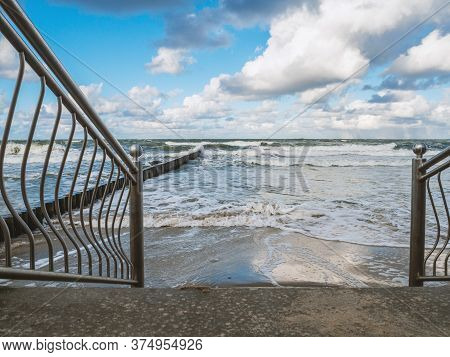 Descent To The Sea By Stairs In A Storm. Metal Fences In The Foreground And Breakwaters In The Backg