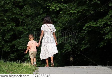 Mother And Kid Are Walking Down The Path Holding Hands. Young Woman In Dress Lead Little Boy In A Su