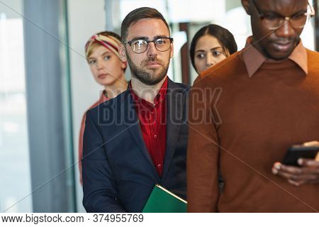 Waist Up Portrait Of Business People Standing In Line In Office, Focus On Mature Bearded Businessman