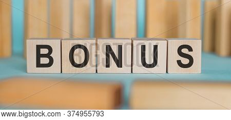 Word Bonus From Wooden Cubes On Blue Table Wooden Background. Concept Bonus Is Any Financial Compens