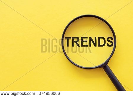 Trends Text Written On Magnifier Glasses, On Yellow Background. Main Trend Of Changing Something. Po
