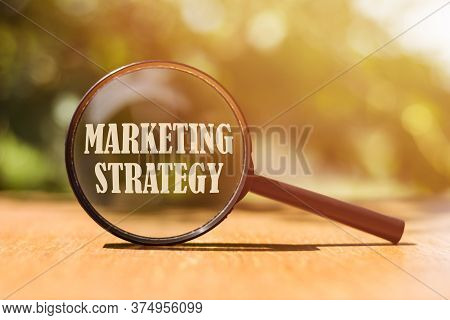 Magnifier Glass With Text Marketing Strategy On Wooden Table In Sunlight. Planning Marketing Strateg