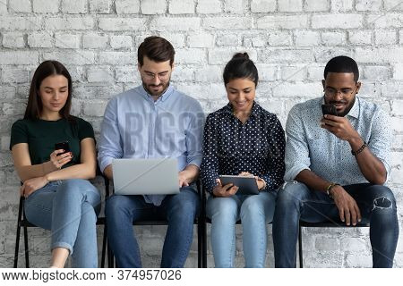 Multiracial Young People Sit Indoor With Diverse Electronic Mobile Devices