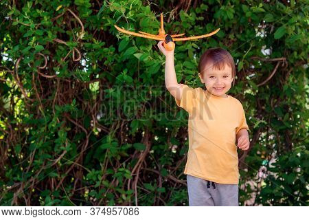 Toddler Boy Playing Solo With Orange Toy Airplane In Garden Or Courtyard. Green Leaves Behind. Happy