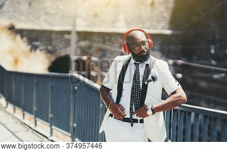 An Elegant Adult Bald Bearded Black Guy In A Fancy White Suit With A Necktie And Red Wireless Headph