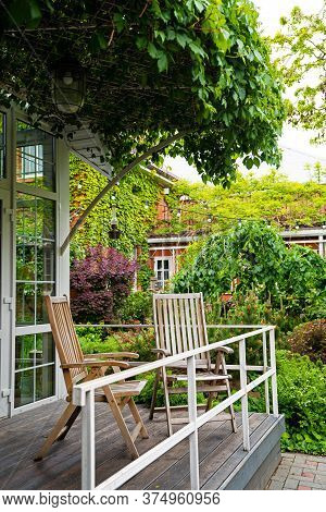 Landscaping. Spring Garden In The Yard. House Entwined With Ivy. Wooden Folding Chairs