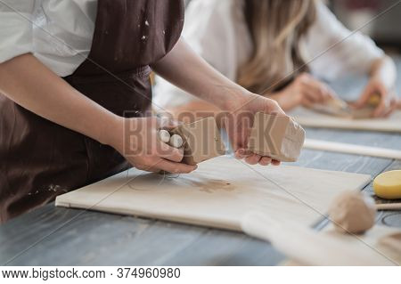 White Clay Preparation For Work. Cutting Layers Of Clay Pieces For Sculpting In The Workshop Of A Po