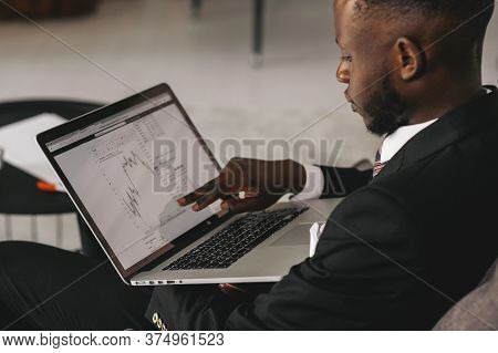 Black Businessman Using Laptop For Analyzing Data Stock Market, Forex Trading Graph, Stock Exchange