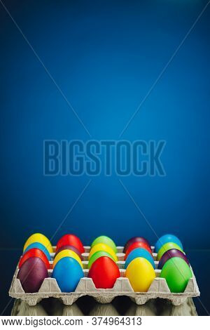 Easter festive multicolor eggs carton, blue background with copy-space