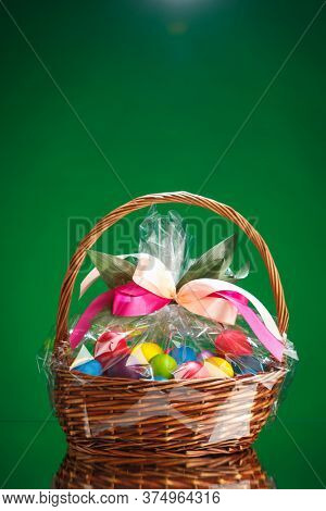 Easter gift basket with multicolor eggs, green background