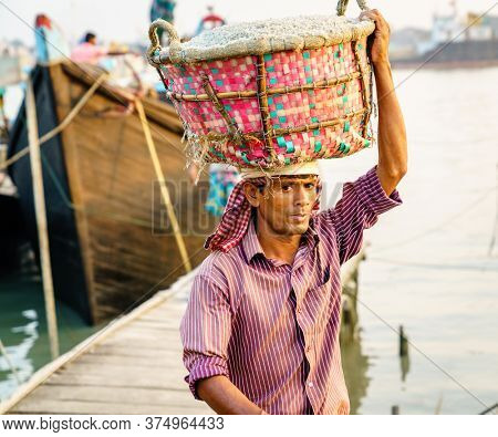 Chittagong, Bangladesh, December 22, 2017: Manual offloading of salt from a boat at the Karnaphuli River port in Chittagong, Bangladesh