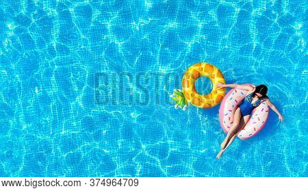 Pool Water Texture Background With A Woman On The Inflatable Water Toys. Directly Above. Top View Fr