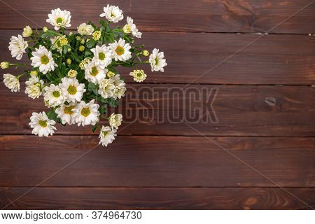 A Bouquet Of White Bush Chrysanthemums On A Wooden Table In The Upper Left Corner.