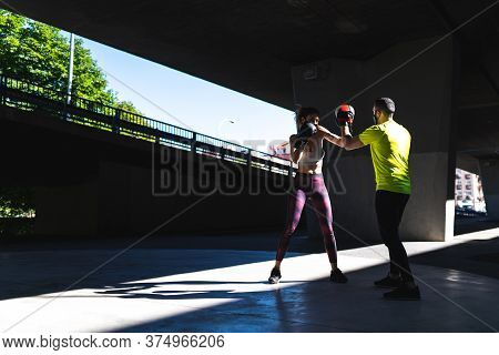 Spanish Woman Training Boxing With Coach Outdoors. Beautiful Woman Boxing With Personal Trainer. Per