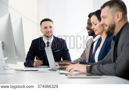 Multy-ethnic group of business people sitting at the office desk and working together