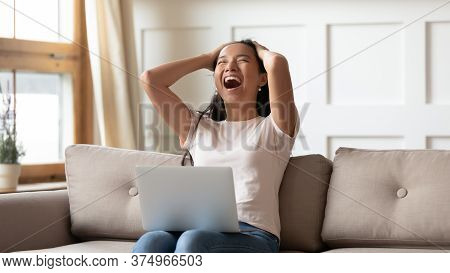 Overjoyed Young Asian Ethnic Woman Reading Email With Unbelievable News.