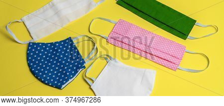 Five Colored Different Medical Masks On Yellow Isolated Background. Hygienic Antimicrobial, Antivira