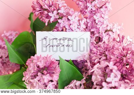 Inscription I Love You On Russian On A White Gift Card In A Beautiful Bouquet Of Lilac Flowers