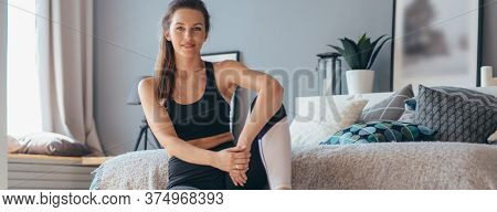 Portrait Of Young Woman Sitting On Bed At Home.