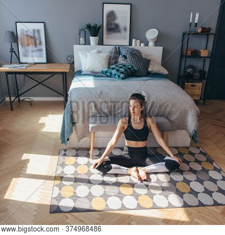 Fitness Woman In Sports Clothes Sitting On Floor In Bedroom.