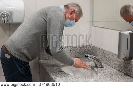 Senior man washing his hands in a public restroom, Coronavirus prevention concept