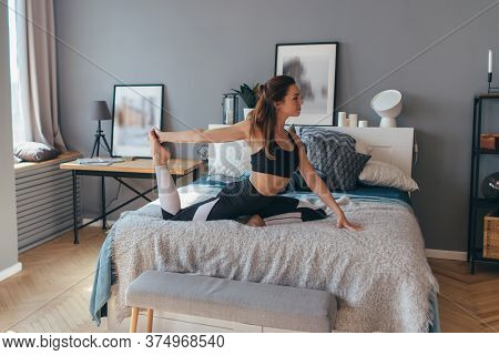 Young Woman Exercising At Home. Morning Workout In Bedroom.