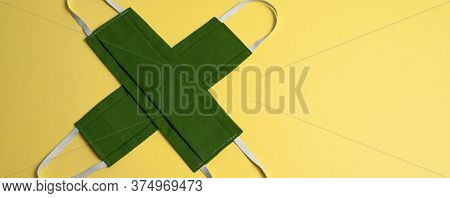 Two Colored Medical Masks In Shape Of Cross On Yellow Background, Isolated. Green Hygiene, Antiviral