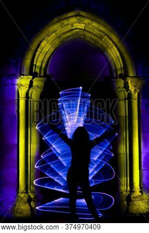 Silhouette Of A Woman With Led Light. Curved Abstract Shape Made With A Light Saber Blue. Lightpaint
