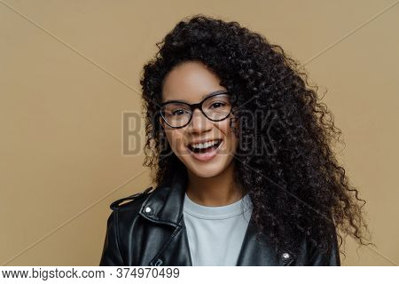 Headshot Of Cheerful African American Woman With Dark Curly Hair, Has Pleased Face Expression, Joyfu