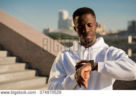 Young serious sportsman of African ethnicity looking at smartwatch on left wrist while going to jog in the morning in urban environment
