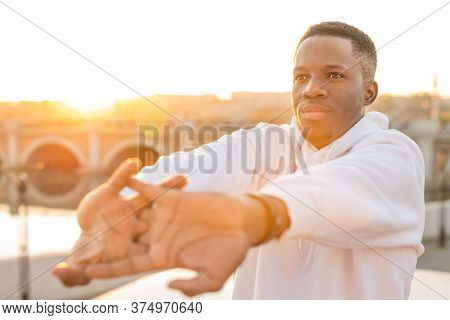 Young sportsman of African ethnicity stretching his arms in front of himself while exercising outdoors on background of bridge and waterside