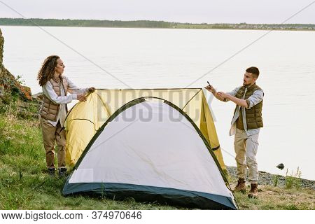 Contemporary young hikers putting tent on the ground by waterside and stretching textile roof over top while preparing for night