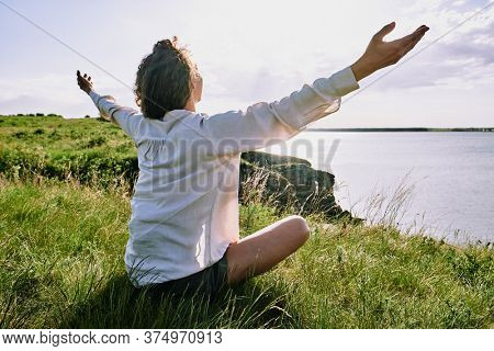 Happy young relaxed female with dark wavy hair and outstretched arms sitting on the ground covered with green grass in front of lake