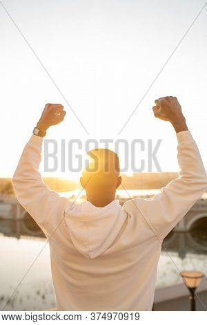 Back view of young winner of African ethnicity making triumph gesture after achievement in sports while standing against sky and river